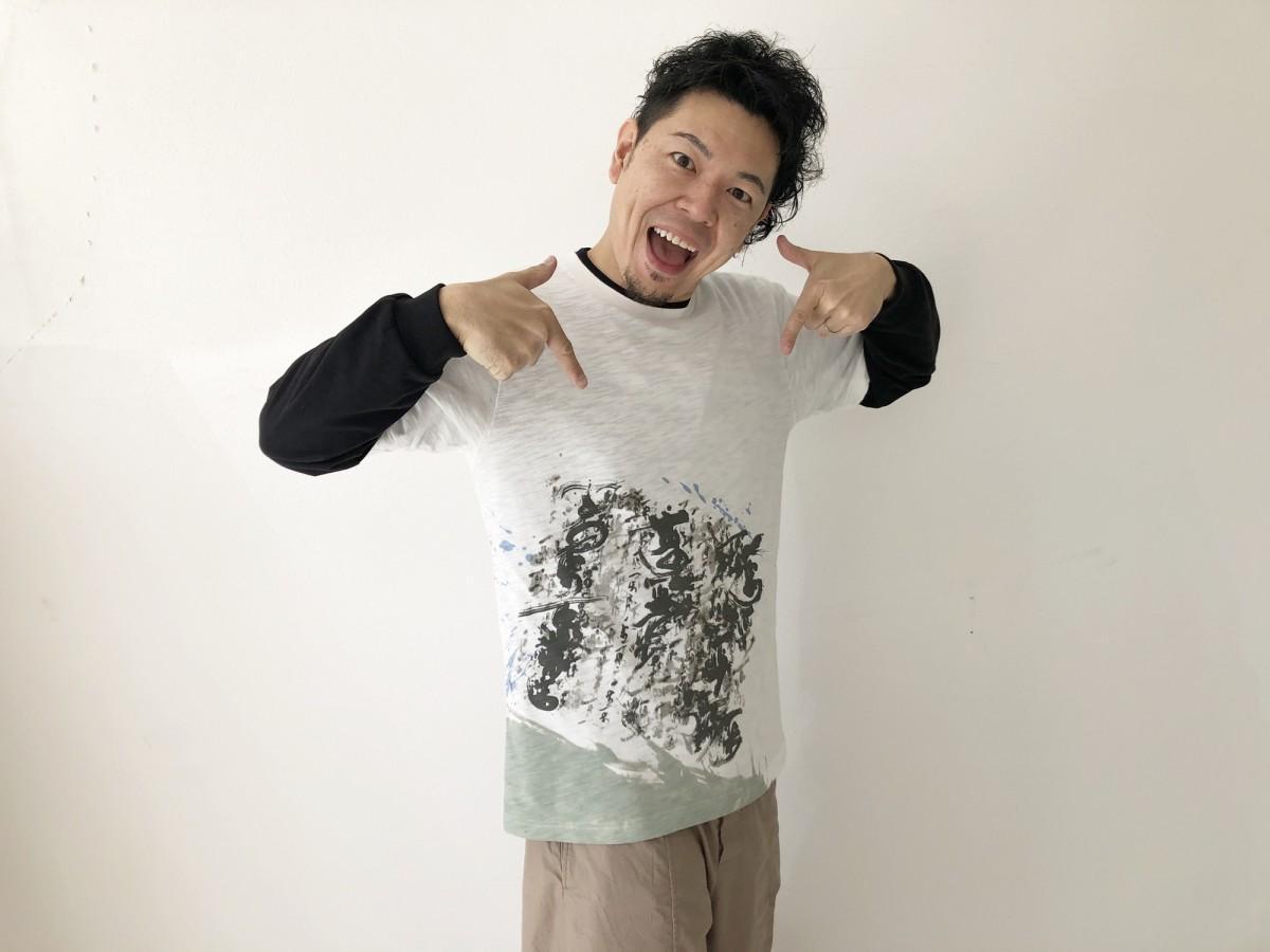自身の作品がデザインされたTシャツを着る山口芳水さん