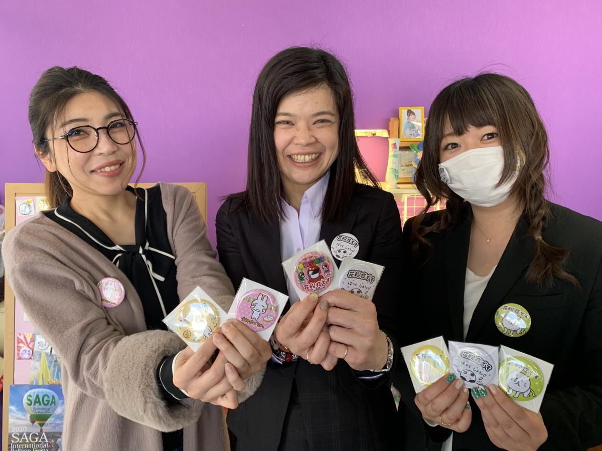 「花粉症主張缶バッジ」を手にするHANAデザイン事務所の北島久美子さん(中央)、狩峰ゆかりさん(左)、坪上純奈さん(右)