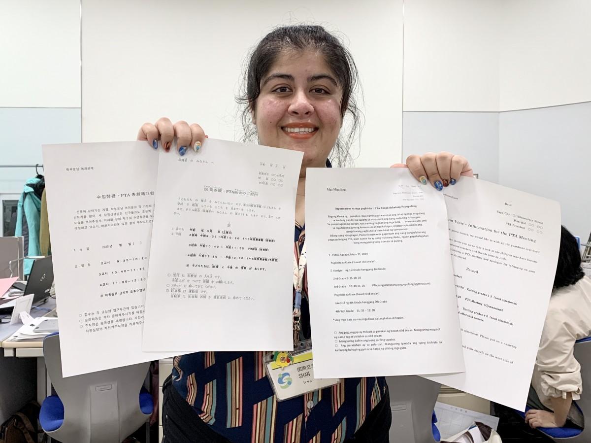 多言語翻訳した文書を手にする佐賀市国際課国際交流員のシャン・ゼディさん