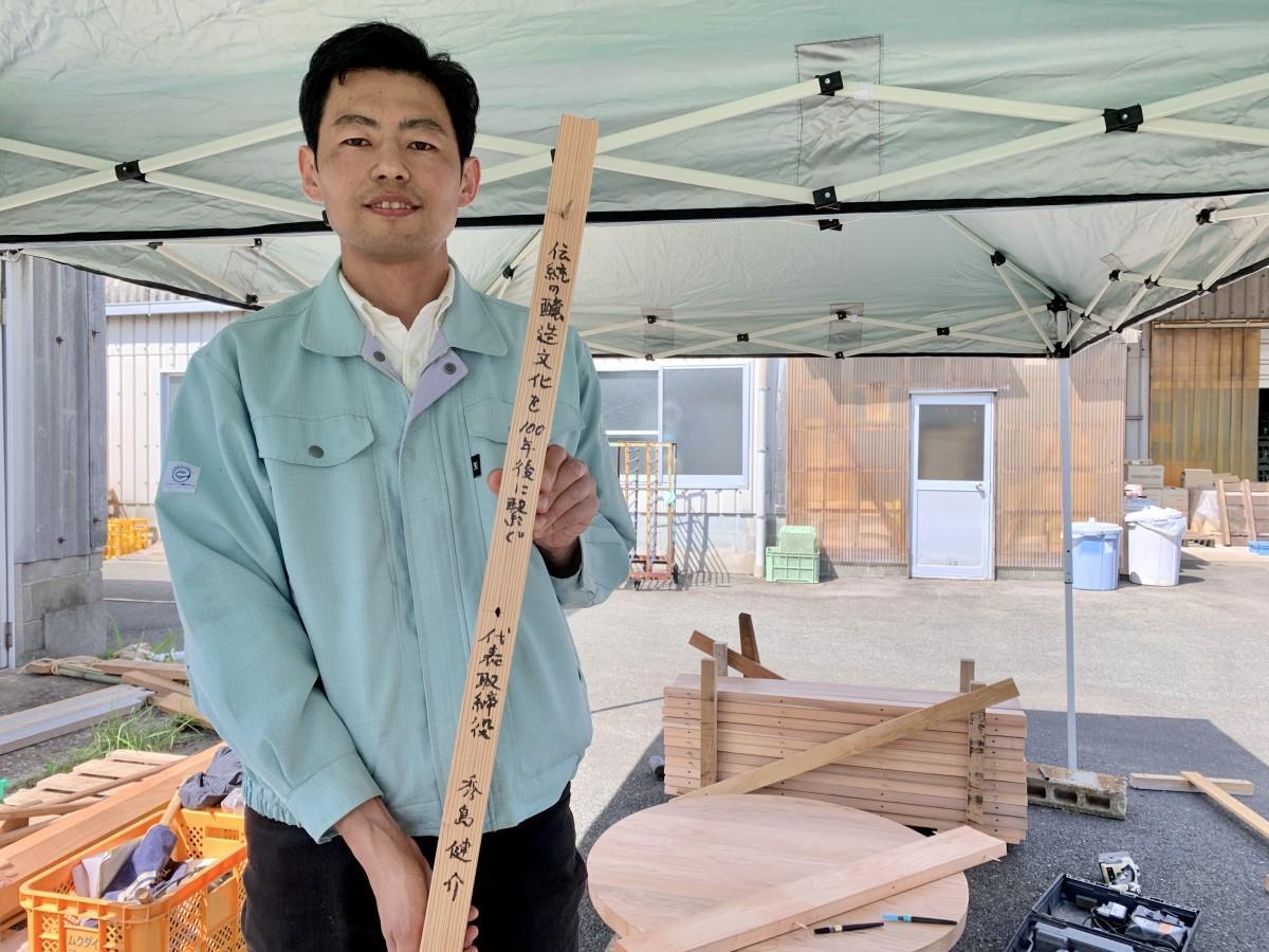 木おけに使う杉の側板、設置面にメッセージを書いた「丸秀醤油」秀島健介社長