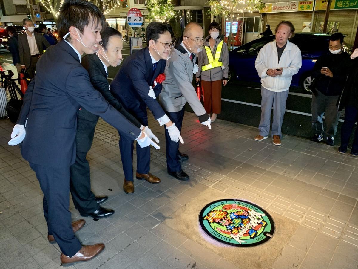 秀島敏行佐賀市長(右)や、「スクウェア・エニックス」市川雅統プロデューサー(右から2人目)らの除幕で披露された「ロマンシング佐賀マンホール」