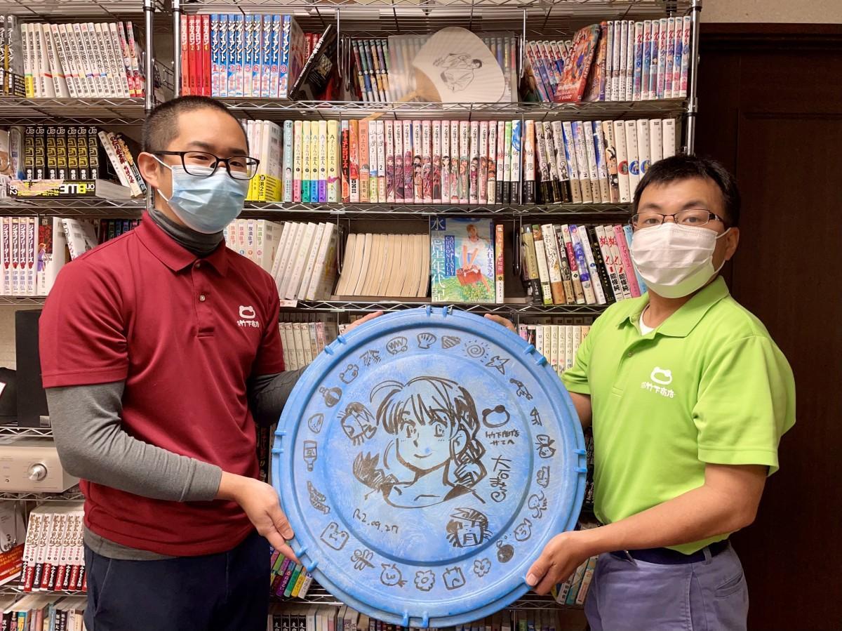 漫画家・大石まさるさんが漫画などを描いた漬物用容器「4斗樽」のフタを手にする「竹下商店」の三木雄太さん(左)と久保田翔さん(右)