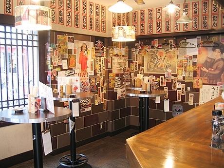 「串焼き肉料理 大黒」の店内。壁はレトロなビールのポスター、日本酒や焼酎のラベルで飾られる。