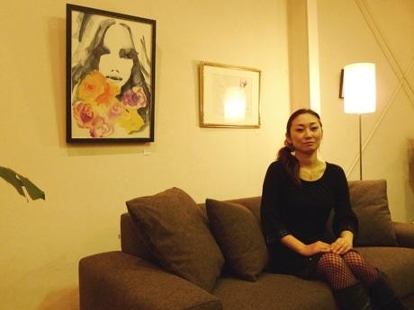 自身の作品の前で「NOyes」のソファに座る吉岡さゆりさん