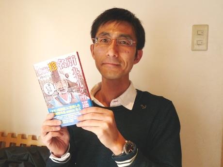 サカエ経済新聞の取材に応える大竹敏之さん。「東海珍名所九十九カ所巡り」を手に