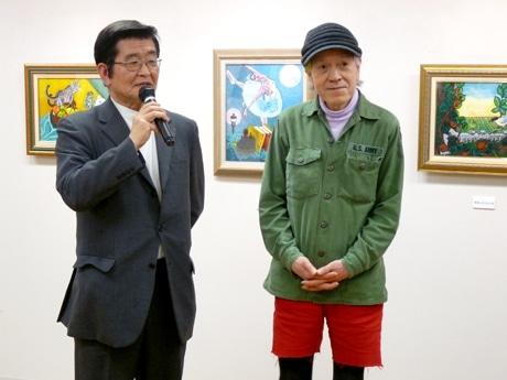 オープニングの挨拶をする、田家阿希雄さん(左)と志茂田景樹さん(右)。志茂田さんの絵の前で