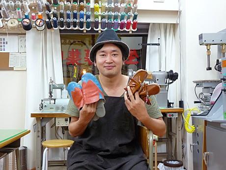 「靴アサオカ工房」をオープンした浅岡さん。手にしているのは手づくりの工房用スリッパと子ども用の靴。