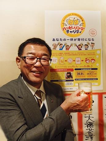 「ハッピーリングチャリティー」を展開する、生ビールを手にしたマルト水谷の梶田知社長