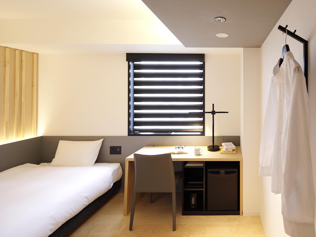 机や椅子、壁面などインテリアの多くに木材を使用し、落ち着きのある客室。写真はシングルタイプの部屋