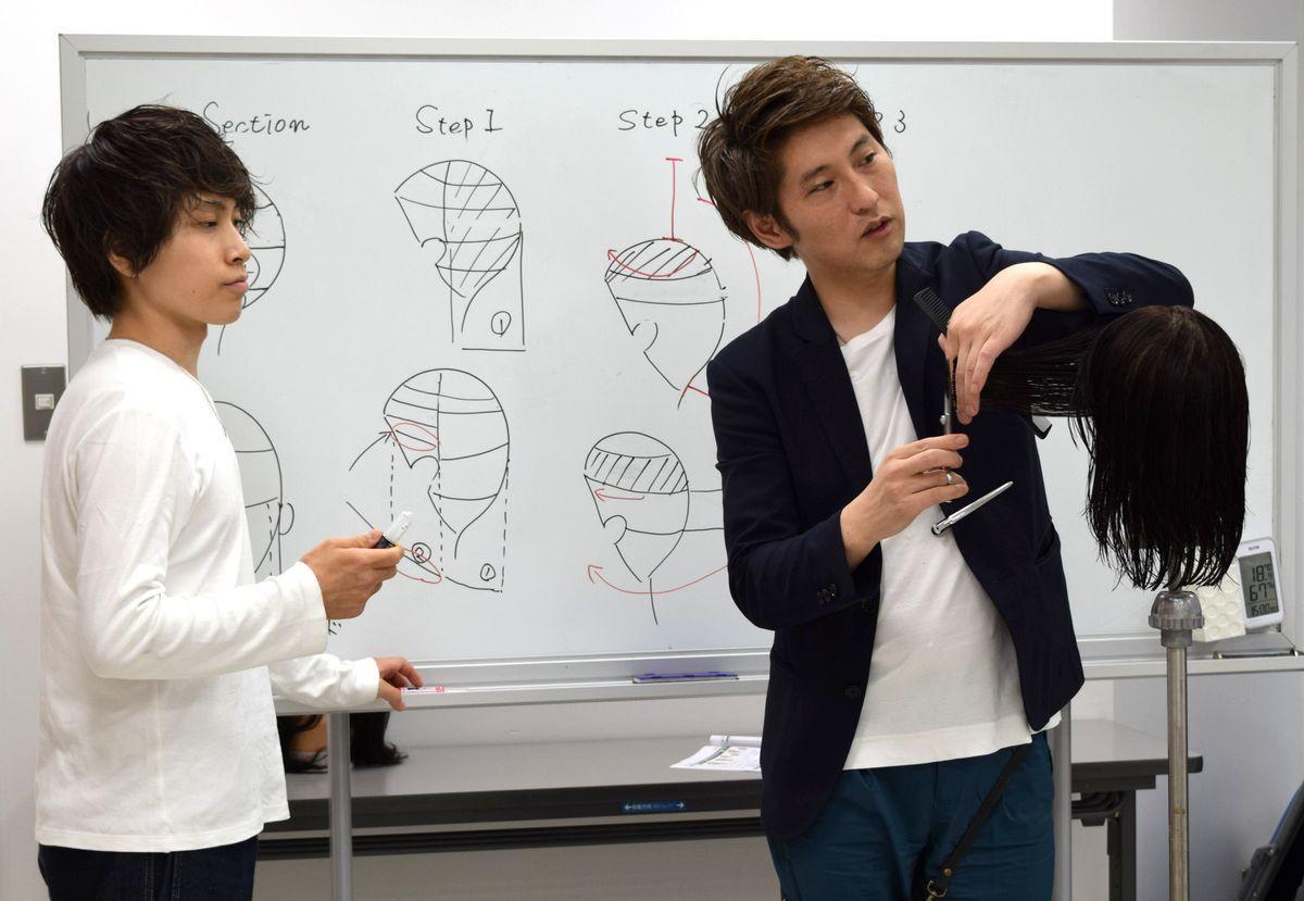 カンボジアで美容技術を指導する山本康雄さん(右)、木下史穏さん。栄の「ASK Academy 名古屋」で行われた事前研修に参加