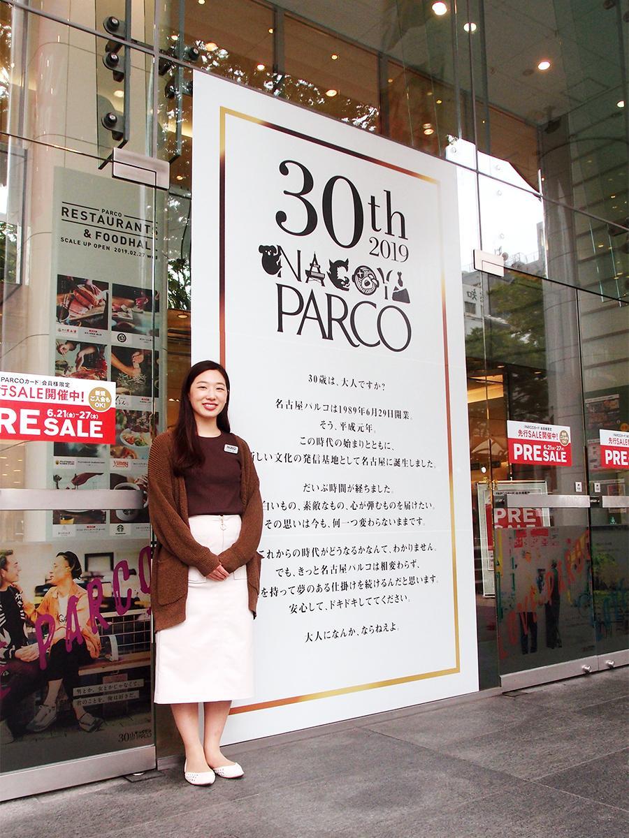 開業30周年のロゴマークとメッセージコピーを記したポスターの前で営業課の貞安遥さん