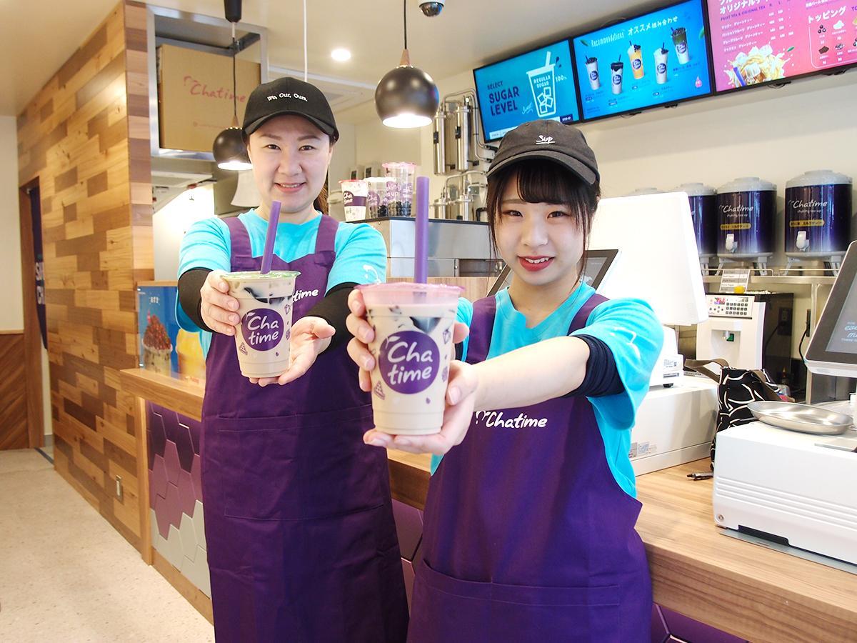 「お薦め」という仙草ゼリーをトッピングしたミルクティーを手に笑顔を見せる蘇欣社長(左)