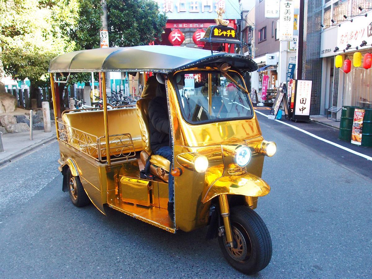大須商店街を背景に「幸運の金シャチ号」