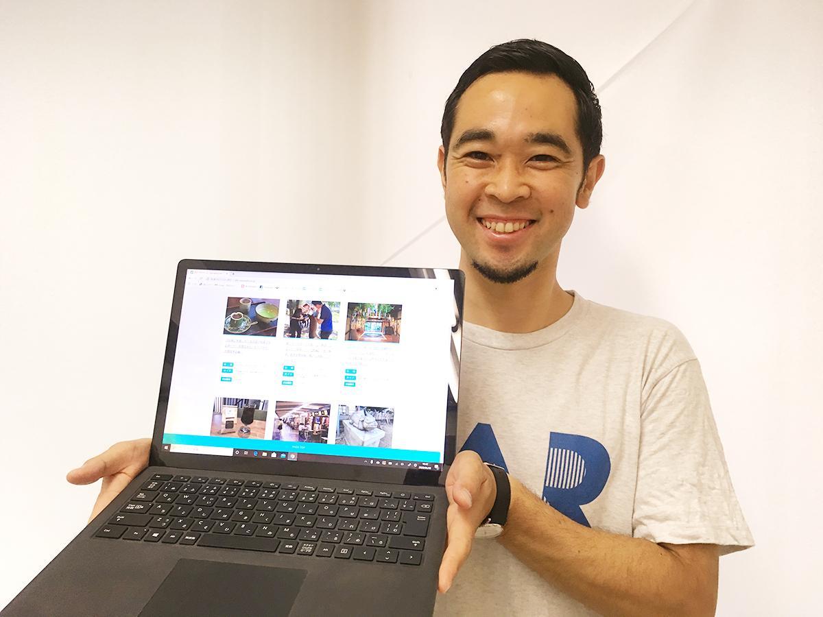 夏のツアーを掲載した「大ナゴヤツアーズ」のホームページ画面を手に笑顔を見せる代表の加藤幹泰さん