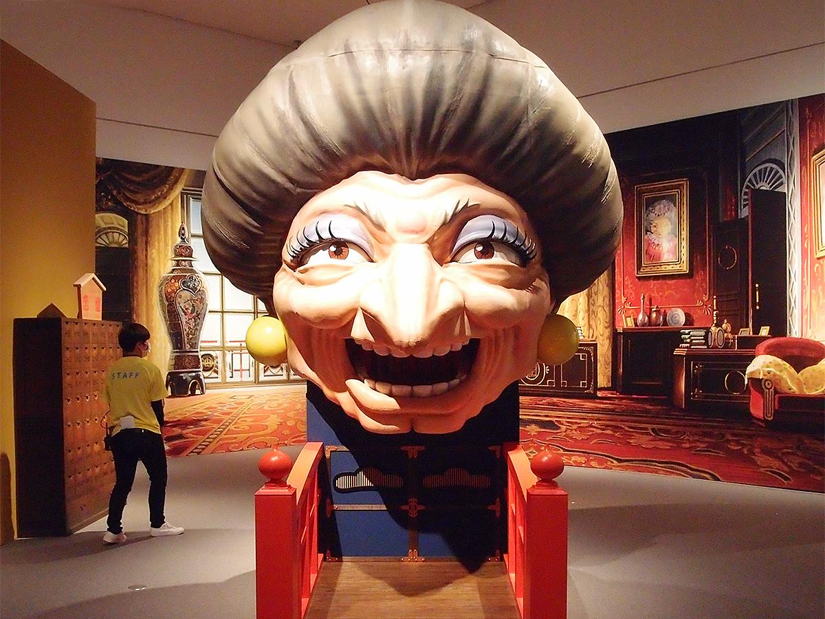 「銭婆」の顔の大きな立体展示物。反対側には「湯婆婆」の顔があり、両方の口部分からおみくじが引ける仕掛けも © Studio Ghibli
