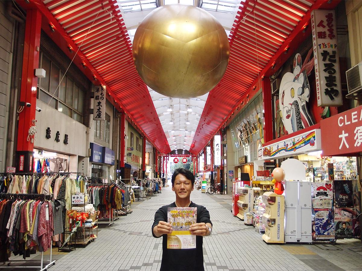 アーケードに大きな「金の玉」を背景に大須商店街連盟青年部副部長の井上誠さん