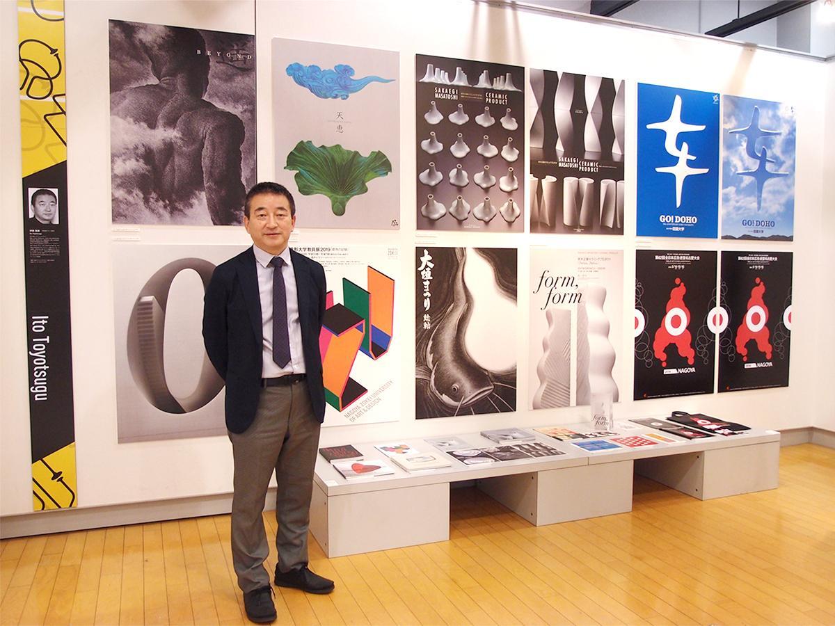 「7 GRAPHIC DESIGNERS IN NAGOYA 2020」を企画した名古屋造形大学教授で副学長の伊藤豊嗣さん。背景は自身のデザインワーク