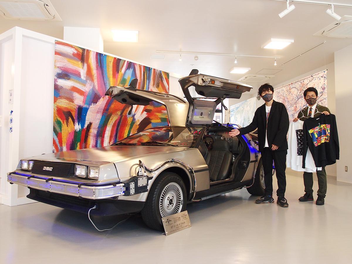 ゴミ(衣料品)をリサイクルして得られたバイオ燃料で動く「世界で1台のデロリアン」の前で、ヘラルボニーの松田崇弥社長(左)と店長の大田雄之介さん。後ろは三重のアーティストの作品