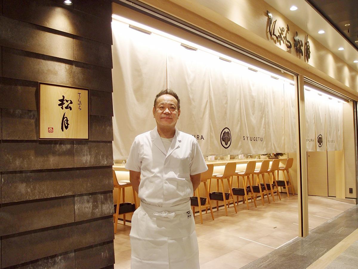 移転した新店舗の前で笑顔を見せる「松月」の桑原幸秀社長