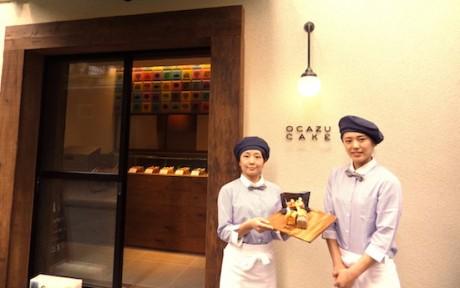 店舗前で色とりどりのおかずケーキを手に持つ店舗スタッフの渡会瞳(わたらい ひとみ)さん(左)と松枝あき子さん(右)。温かみのあるライトとロゴが目印