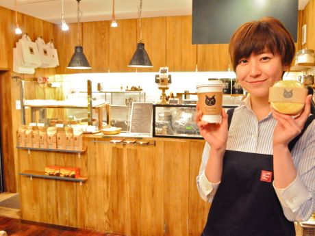 コーヒーと名物の「円パンサンド」を持つスタッフの黒田さん