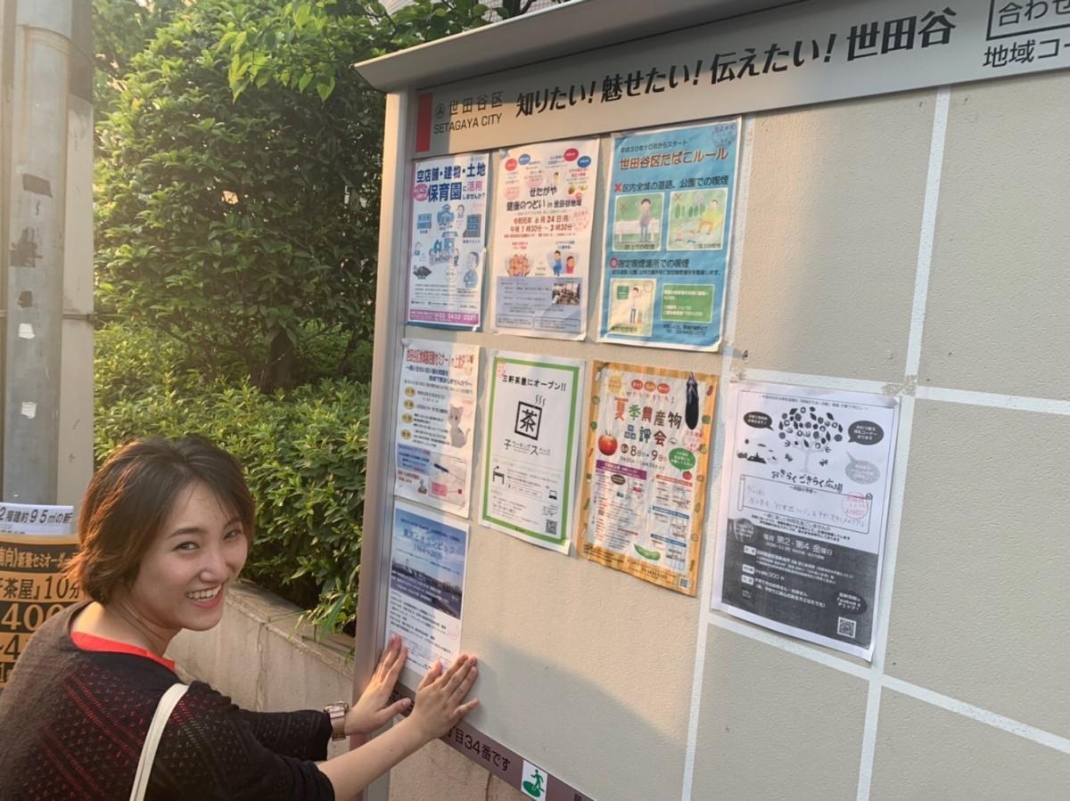 広報活動として三軒茶屋でポスター貼りをする学生