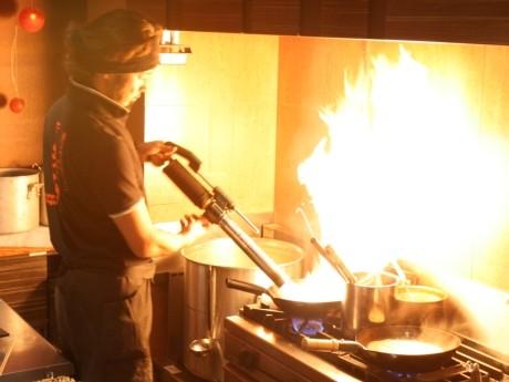 火炎放射器(高火力バーナー)で調理している様子