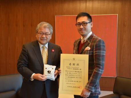 授与式の上田文雄市長と商品を企画したノースユナイテッドの高橋廣行社長(右)