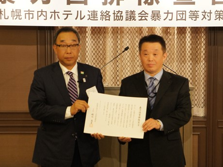 暴力団等排除宣言を手にする桶川会長(左)と北海道警察本部・廣瀬課長(右)
