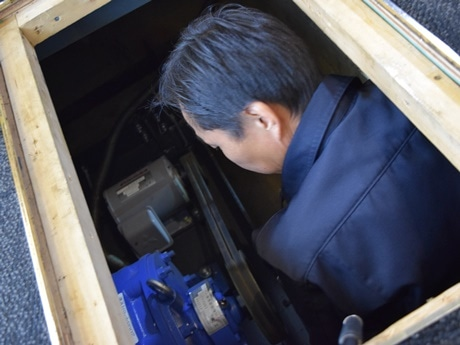 床下の電気モーターを点検する従業員