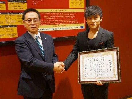新村卓実奥尻町長(左)から表彰状を受け取る厂原時也さん(右)