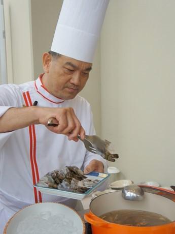 「トムヤムクンスープ」の調理実演を行うシェフ