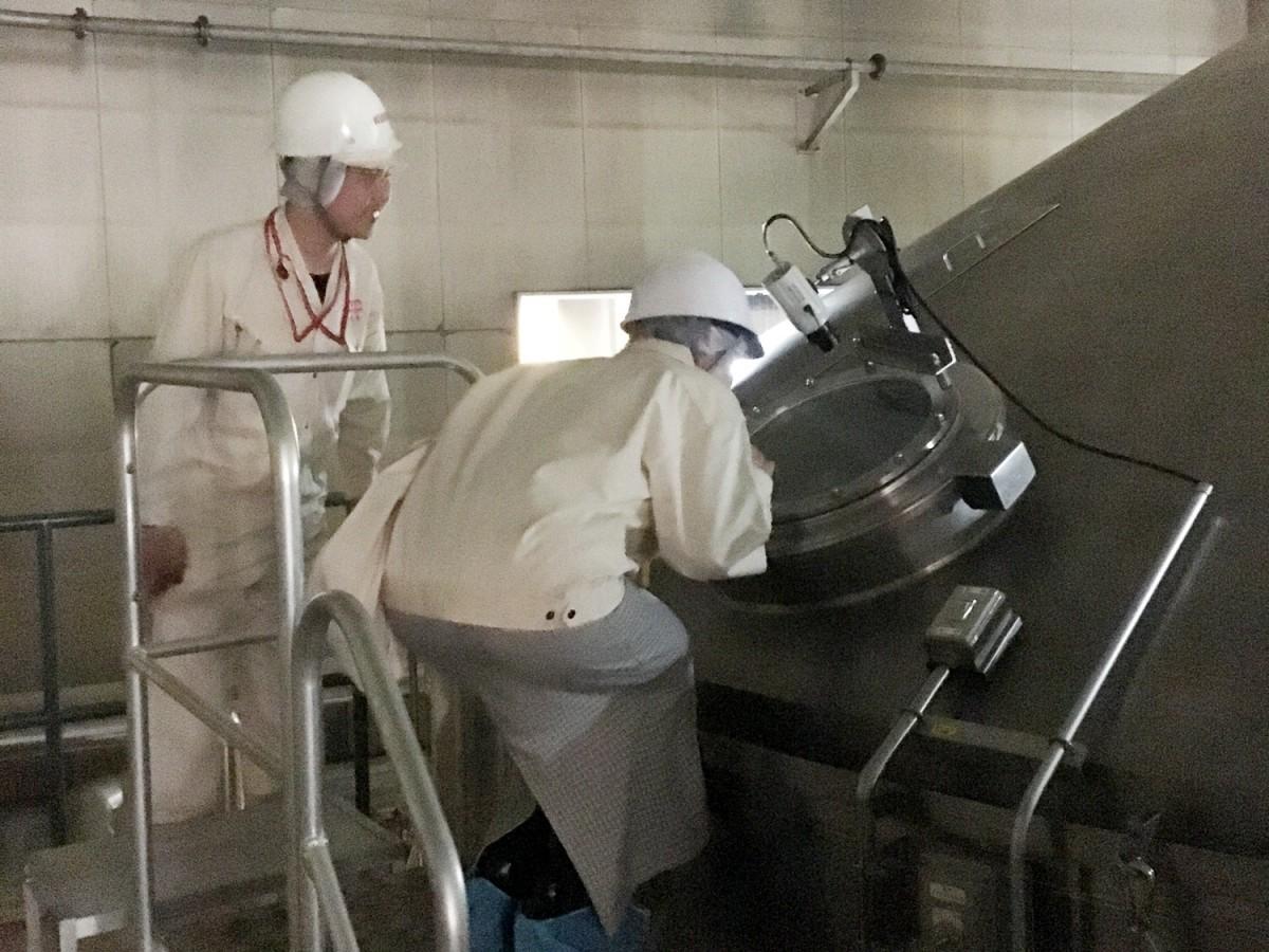 「キリン一番搾り」を製造中の仕込み釜をのぞく見学者