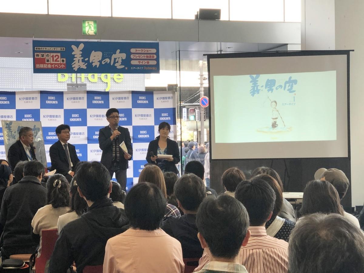 「義男の空」12巻の出版イベントであいさつする田中宏明社長