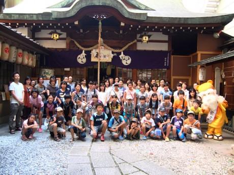 少彦名神社の境内で記念撮影する「親子おくすり教室」の参加者とゆるキャラ「神農さま」