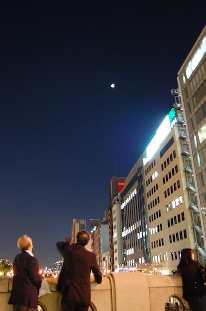 皆既月食を観察する会社帰りのサラリーマンたち