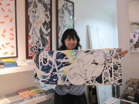 オリジナルブランド「星華集」の人魚姫モチーフの手ぬぐいを持つ西山さん