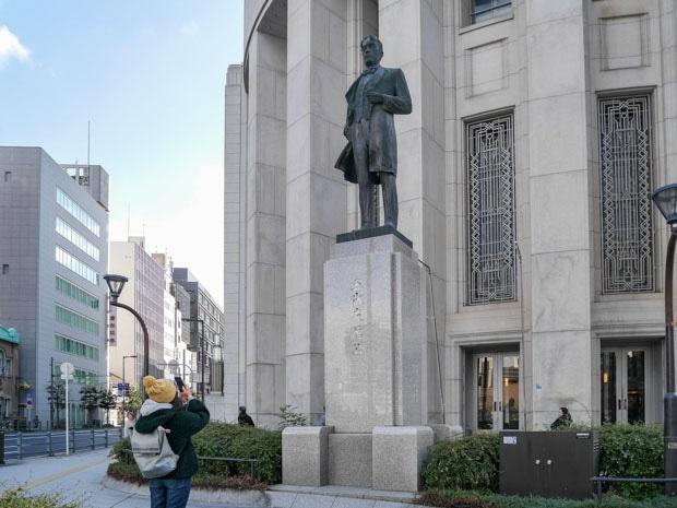 大阪取引所前の五代友厚像にカメラを向ける女性ファン
