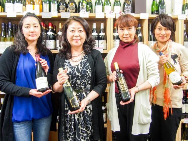 ずらりと並ぶ店内のワインを背景に、人気のワインを持って並ぶ社長の酒井さん(左から2番目)とスタッフ