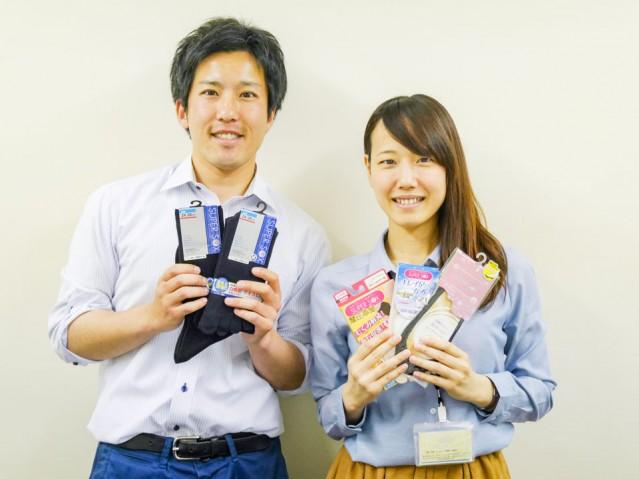 (右から)参加賞のスーパーソックスを手に持つ広報担当の淺井さんと伴野さん