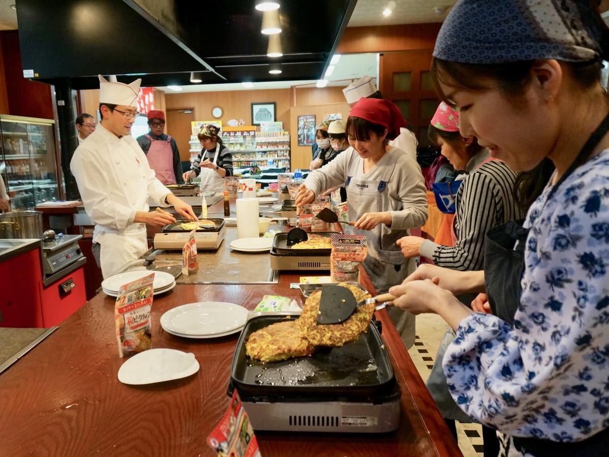 お好み焼きを作る参加者と講師の川本和晴さん