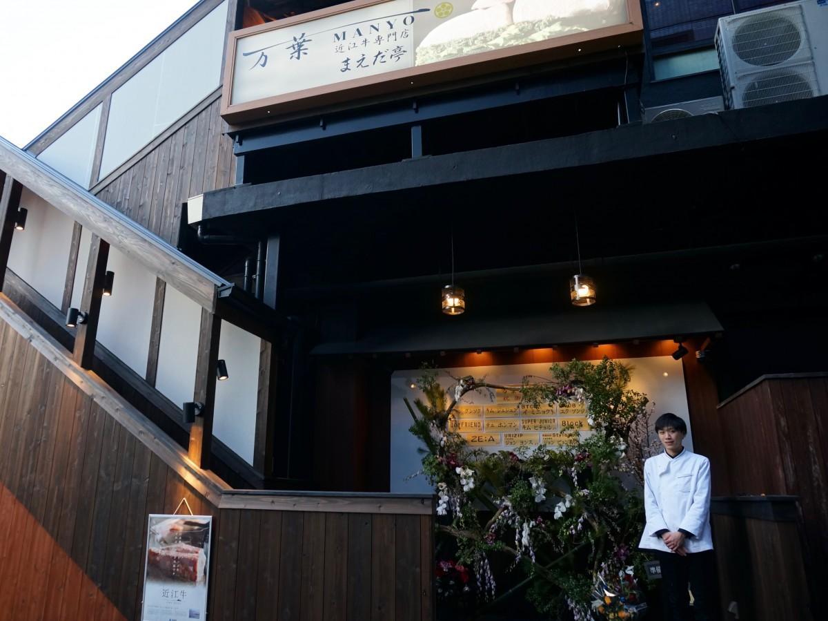 店の前に立つスタッフの村山烈さん