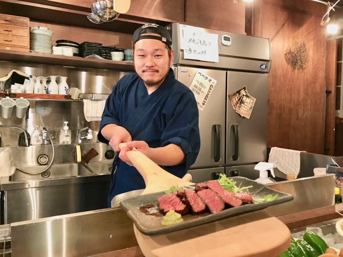 しゃもじで料理を運ぶ店主の橋本学さん