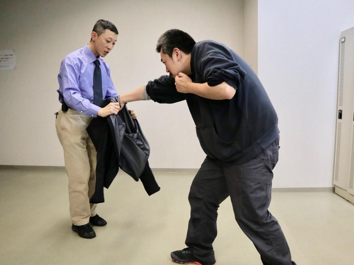 危険からの逃げ方を実演する真坂洋之さん(左)