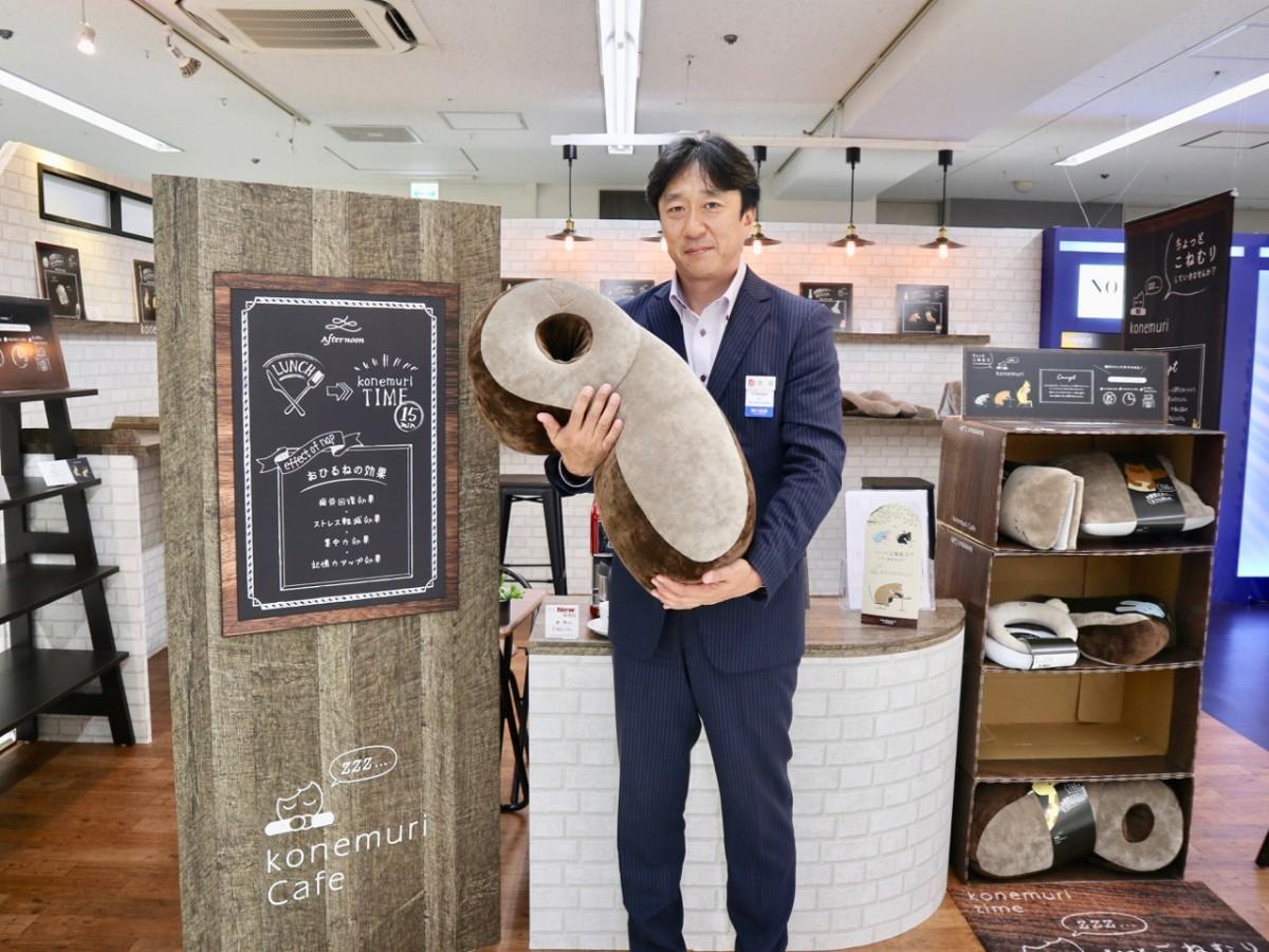 「きりん」の枕を抱える吉田幸司課長