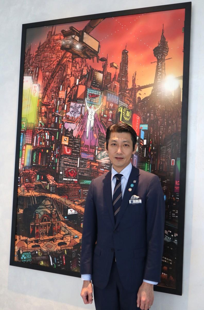 総支配人の若林健一さん。後ろは未来の大阪を描いたというグラフィックアート