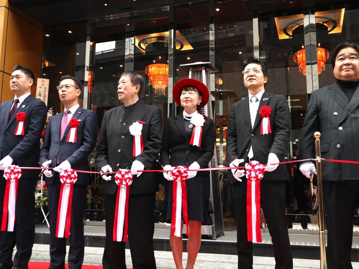 テープカットに臨む元谷芙美子社長(右から3人目)と元谷外志雄代表(左から3人目)