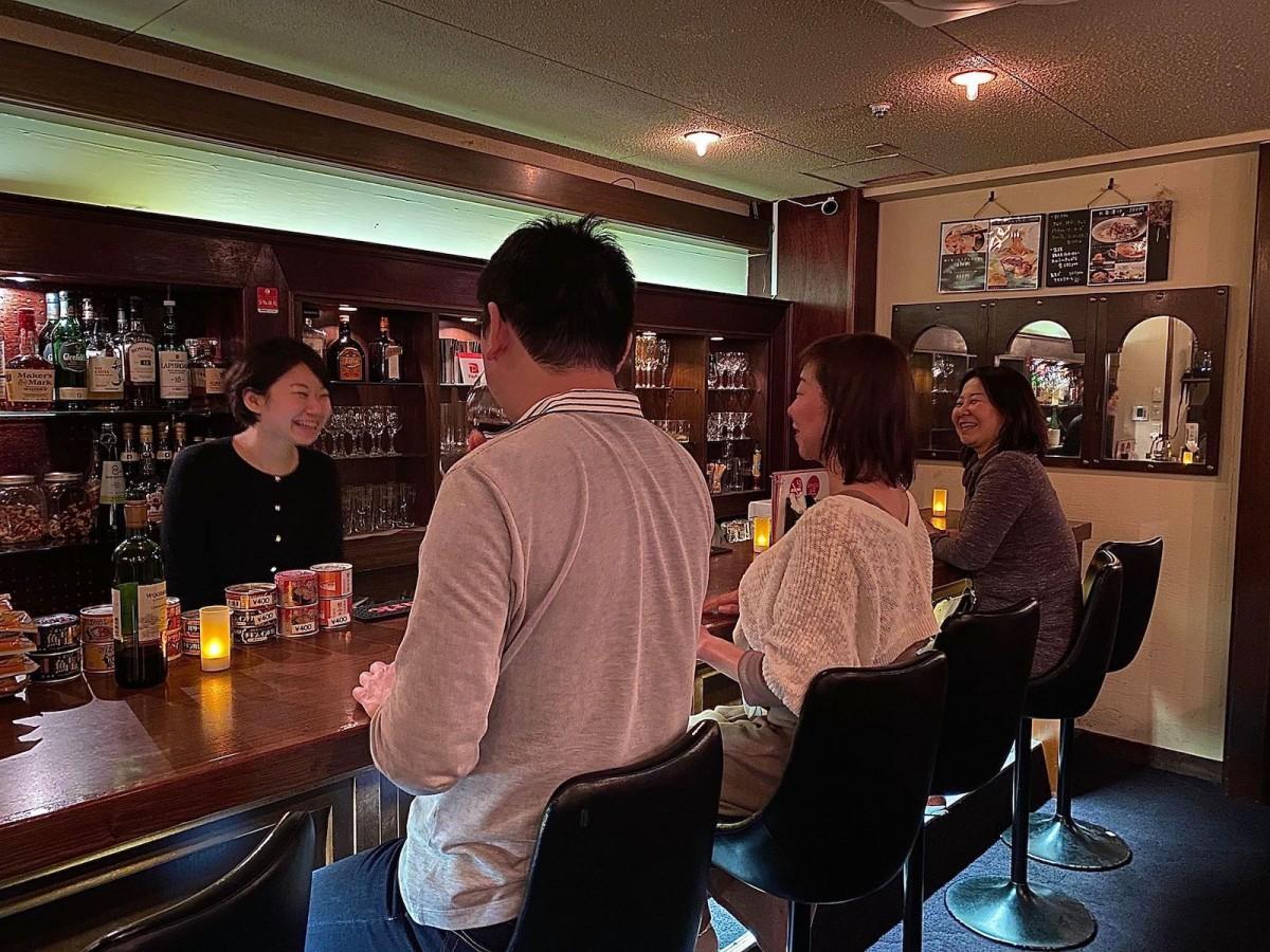 コナイト酒場カウンターで客を迎える曜日店長