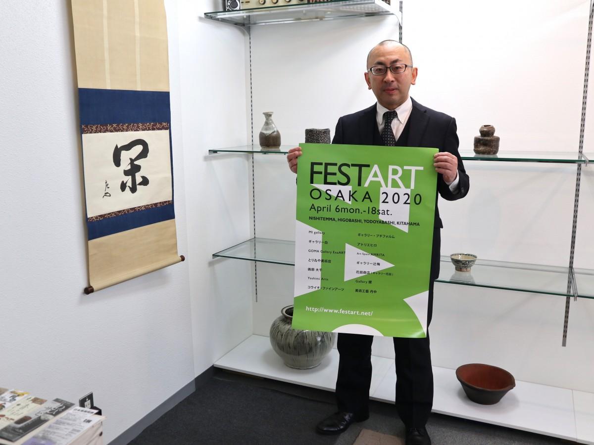 作品の前でポスターを持つ花田さん