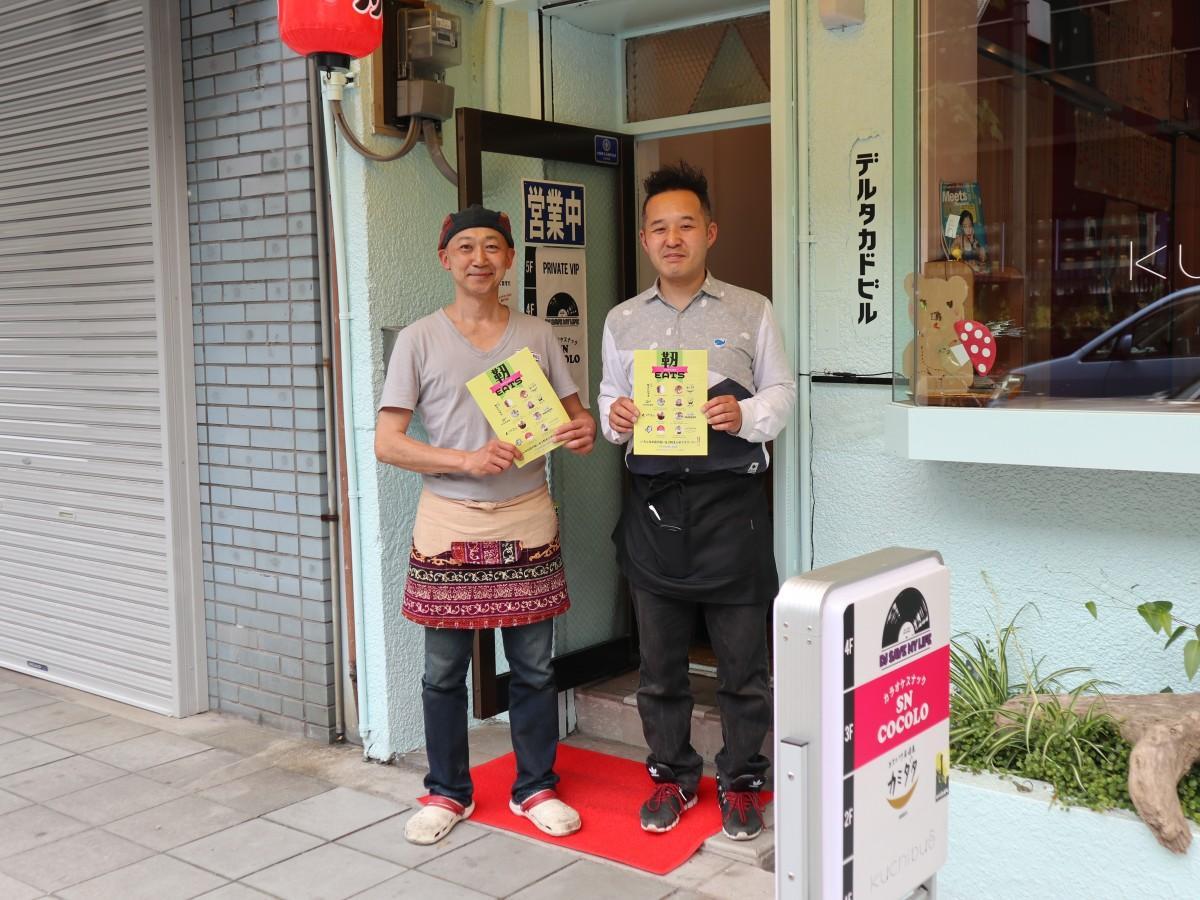 注文受付センターのあるデルタカドビル前で立つ中野さん(右)と網田さん